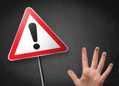 Happy smiley fingers looking at triangle warning sign with excla — Stock Photo