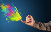Colorful splashes are coming out of gun shaped hands — Stock Photo
