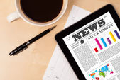 Tablet pc shows nieuws op scherm met een kopje koffie op een bureau — Stockfoto