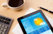 Previsioni meteo di tablet pc visualizzando sullo schermo con una tazza di caffè — Foto Stock