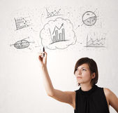 Young lady sketching financial chart icons and symbols — Stock Photo