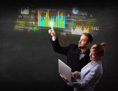 Young business couple touching colorful charts and diagrams — Stock Photo