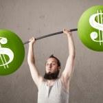 Skinny guy lifting green dollar sign weights — Stock Photo #38825757