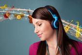 Jeune femme avec un casque d'écoute de la musique — Photo