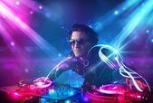 Energický dj mixování hudby s výkonné světelné efekty — Stock fotografie