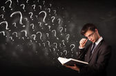 Young man reading a book with question marks coming out from it — Stock Photo