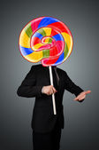 Businessman holding a lollipop — Stock Photo