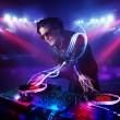 Disc jockey playing music with light beam effects on stage — Stock Photo #39292777