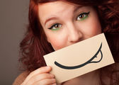 年轻漂亮的姑娘与绘图的微笑举行白卡 — 图库照片