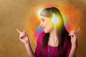 Mladá žena se sluchátky poslechu hudby — Stockfoto