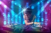 Dj mezclando música en una discoteca con luces azules y púrpuras — Foto de Stock