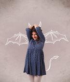 年轻女孩的恶魔之角和绘图的翅膀 — 图库照片