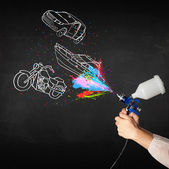 Man with airbrush spray paint with car, boat and motorcycle draw — Stock fotografie