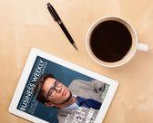 планшетный пк, показывая журнал на экране с чашкой кофе на d — Стоковое фото