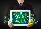 Person holding tablet with green media icons and symbols — 图库照片