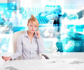 Business person at desk with modern tech images at background — 图库照片