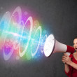 Stock Photo: Young girl yells into a loudspeaker and colorful energy beam com