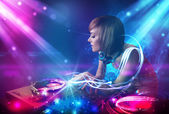 Energetic Dj girl mixing music with powerful light effects — Stock Photo