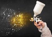 работника с аэрографом живописи с светящиеся золотая краска — Стоковое фото
