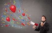 Jonge kerel plezier, schreeuwen in megafoon met ballonnen — Stockfoto