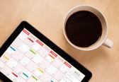 Tablet pc-ergebnis-kalender auf dem bildschirm mit einer tasse kaffee auf ein d — Stockfoto