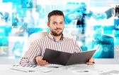 Business person at desk with modern tech images at background — Stock Photo