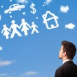 Businessman daydreaming with family and household clouds — Stock Photo