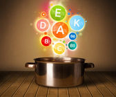 Colorful vitamins coming out from cooking pot — Stock Photo
