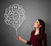 Woman holding a bunch of smiling balloons — Stock Photo