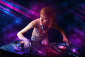 Young DJ playing on turntables with color light effects — Stock Photo