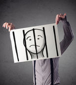 Businessman holding a paper with a prisoner behind the bars on i — Stock Photo