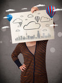 Woman holding a cardboard with cityscape in front of her head — Stock Photo