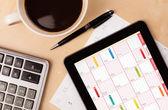 Počítače tablet pc ukazuje kalendář na obrazovce s šálkem kávy na d — Stock fotografie