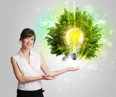 Young girl presenting idea light bulb with green tree — Stock Photo