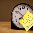 Foto Stock: Post-it note with smiley face sticked on clock