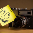 Foto Stock: Post-it note with smiley face sticked on photo camera