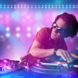 Foto Stock: Disc jockey mixing music on turntables on stage with lights and