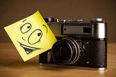 Poznámka: post-it s emotikony nalepený na fotoaparátu — Stock fotografie