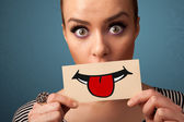 Happy pretty woman holding card with funny smiley — Stock Photo