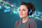 Joven mujer escuchando música con auriculares — Foto de Stock