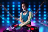 Jovem dj mistura registros com luzes coloridas — Foto Stock