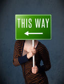 Young woman holding a direction sign — Stock Photo