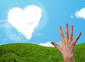 Doigts de smiley heureux en regardant les nuages en forme de coeur — Photo