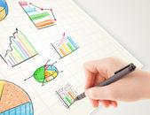 Uomo d'affari grafici colorati e icone di disegno su carta — Foto Stock