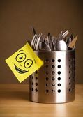 Post-it note with smiley face sticked on cutlery case — Stock Photo