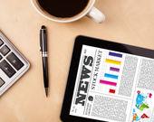 Tablet pc présente des nouvelles sur l'écran avec une tasse de café sur un bureau — Photo