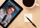 Tablet pc tijdschrift tonen op het scherm met een kopje koffie op een d — Stockfoto
