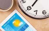 Počítače tablet pc ukazuje předpověď počasí na obrazovce s šálek kafe — Stock fotografie