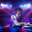 Disc jockey playing music with light beam effects on stage — Stock Photo #41594507