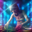 Stock Photo: Dj girl mixing music in a club with blue and purple lights